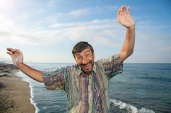 Middle aged man rejoices. A middle aged man rejoices holiday at sea Stock Photo