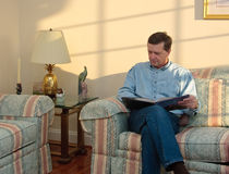 Middle-aged man relaxes on sofa. In modern living room reading a book stock photos