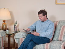 Middle-aged man relaxes on sofa. In modern living room reading newspaper stock photography