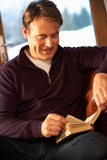 Middle Aged Man Relaxing With Book Sitting On Sofa Royalty Free Stock Photos