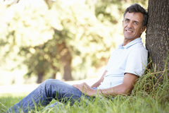 Middle Aged Man Relaxing In Countryside Leaning Against Tree Royalty Free Stock Image