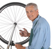 Middle aged Man Repairing Bicycle Stock Images