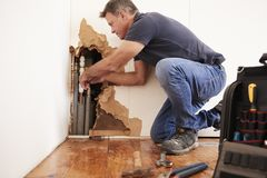 Middle aged man repairing burst water pipe stock image
