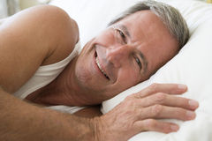 Middle aged man resting bed. Smiling to camera royalty free stock photos