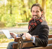 Middle-aged man resting on the bench outdoors. Close-up picture of handsome middle-aged man working in the park. Happy man with fashionable scarf on holding stock image