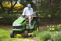 Middle-Aged Man on Riding Lawn Mower. A white middle-aged man on a riding, tractor-style lawn mower, carefully mowing the grass around an attractive flower bed Royalty Free Stock Photo
