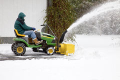 Middle-Aged Man on Riding Snowblower--Side View. Upper middle-aged man on tractor-style riding snowblower clearing snow out of residential driveway.  Snow is Stock Photos