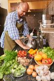 Rinsing ingredients. Middle-aged man rinsing ingredients for the salad Stock Images