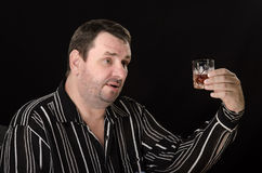 Middle aged man rises glass of brandy. On black background Stock Image