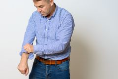 Middle aged man rolling up his sleeves Royalty Free Stock Photos
