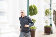 Middle aged man running in the city. Fit middle aged hispanic man jogging outdoors in the city royalty free stock image