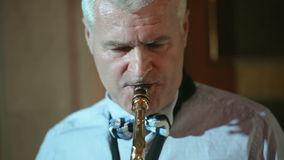 Middle-aged man saxophonist 50 years playing a musical instrument saxophone. stock video footage