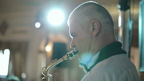 Middle-aged man saxophonist 50 years playing a musical instrument saxophone. stock video