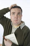 Middle Aged Man Scratching Head. Middle aged men scratching his head while holding book and pen isolated over white background Stock Images