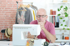 Middle-aged man in a sewing workshop. A middle-aged man in a sewing workshop royalty free stock photo
