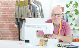 A middle-aged man in a sewing workshop. A smiling middle-aged man in a sewing workshop stock photos
