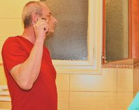 Middle aged man shaving in a bathroom, using electric razor. Senior concept. Mature man at home.  Stock Photo