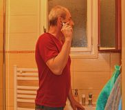 Middle aged man shaving in a bathroom, using electric razor. Senior concept. Mature man at home.  Stock Image