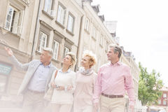 Middle-aged man showing something to friends while walking in city Stock Photo