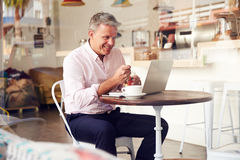Middle aged man sitting in a cafe Stock Photos