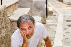 Middle-aged man sitting in medieval town alleys Royalty Free Stock Photo