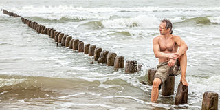 Middle-aged man sitting near the sea Stock Photo