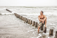 Middle-aged man sitting near the sea Stock Photos