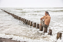 Middle-aged man sitting near the sea Royalty Free Stock Photography