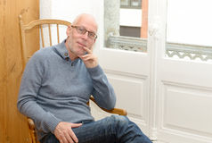 Middle-aged man sitting near a window. A portrait of a middle-aged man sitting near a window Royalty Free Stock Photos