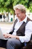 Middle aged man sitting outside using laptop Stock Image