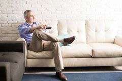 Hispanic mature man watching tv at home. Middle aged man sitting on sofa changing the channels of television with remote control while watching tv at home royalty free stock photos