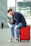 Middle aged man sitting on suitcase using mobile phone. Portrait of middle aged man sitting on suitcase and sending text message Royalty Free Stock Photography