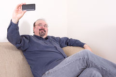 Middle-aged man sitting and taking selfie pictures Stock Photos