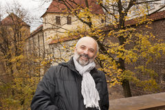 A middle-aged man smiling. On a background of autumn trees in the Prague Castle Royalty Free Stock Photos