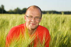 Middle-aged man smiling behind hay.  Royalty Free Stock Photography