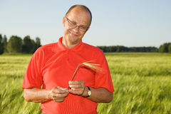 Middle-aged man smiling on a field. Hay in his hand Royalty Free Stock Photography