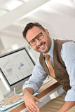 Middle-aged man smiling at office. Middle-aged businessman with eyeglasses in office Stock Photography