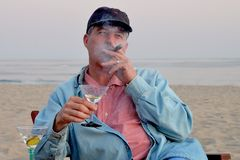 Middle aged man smoking cigar and drinking martini on the beach. Royalty Free Stock Photos