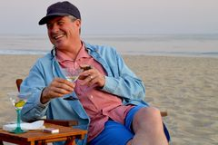 Middle aged man smoking cigar and drinking martini on the beach. Stock Images