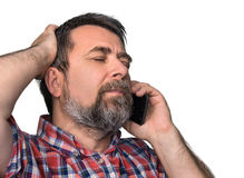 Middle-aged man speaks on a mobile phone. Hard talk. Middle-aged man with closed eyes speaks on a mobile phone isolated on white Stock Photos
