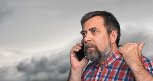 Middle-aged man speaks on a mobile phone. And raised thumb up showing sign ok against dramatic sky with clouds Royalty Free Stock Photography