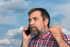 Middle-aged man speaks on a mobile phone. And raised thumb up showing sign ok against the sky with clouds Royalty Free Stock Photo