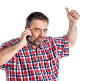 Middle-aged man speaks on a mobile phone. And  raised thumb up showing sign ok. Isolated on white Stock Photography