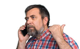 Middle-aged man speaks on a mobile phone. And raised thumb up showing sign ok. Isolated on white Royalty Free Stock Images