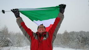 Middle-aged man sport fan waving the Italian flag. In the winter ski slope background stock video