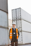 Middle-aged man standing against cargo containers in shipping yard Royalty Free Stock Photography