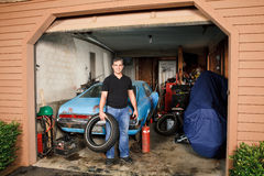 Middle aged man standing in cluttered garage holding a tire Royalty Free Stock Images