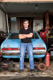 Middle aged man standing and leaning against his old car in his garage. Royalty Free Stock Photos