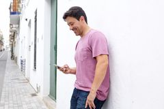 Middle aged man standing outside and reading text message on his mobile phone. Portrait of middle aged man standing outside and reading text message on his Royalty Free Stock Photo