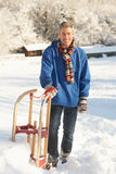 Middle Aged Man Standing In Snowy Landscape. Holding Sledge Stock Photo